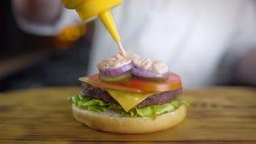 El cocinero hace la hamburguesa jugosa y vierte la salsa picante en ella, haciendo las hamburguesas en el restaurante de los alim metrajes