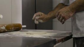 El cocinero hace una base para la pizza en cocina almacen de video