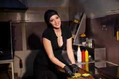El cocinero hermoso de la muchacha prepara la hamburguesa de la cocina fotos de archivo libres de regalías