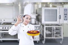 El cocinero sostiene la torta deliciosa - horizontal Imagen de archivo libre de regalías