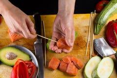 El cocinero implating el filett de color salmón en un pincho Fotos de archivo libres de regalías