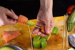 El cocinero implating el filtet de color salmón en un pincho Imagen de archivo