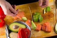El cocinero implating el prendedero de color salmón en un pincho Imagenes de archivo