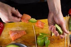El cocinero implating el prendedero de color salmón en un pincho Imágenes de archivo libres de regalías
