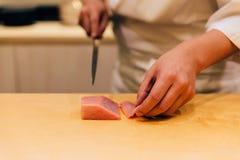 El cocinero japonés de Omakase cortó el Bluefin graso medio Tuna Chutoro en japonés cuidadosamente por el cuchillo en la encimera imagenes de archivo