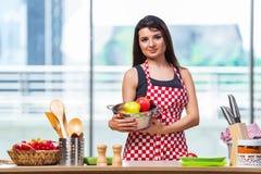 El cocinero joven con las frutas en la cocina Foto de archivo libre de regalías