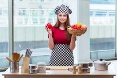 El cocinero joven con las frutas en la cocina Fotografía de archivo libre de regalías