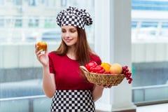 El cocinero joven con las frutas en la cocina Fotografía de archivo