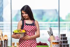 El cocinero joven con las frutas en la cocina Imagenes de archivo