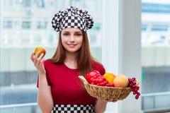 El cocinero joven con las frutas en la cocina Foto de archivo