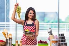 El cocinero joven con las frutas en la cocina Imagen de archivo