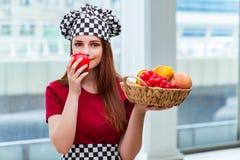 El cocinero joven con las frutas en la cocina Imagen de archivo libre de regalías