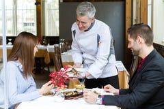El cocinero les presenta el segundo curso a un par en el restaurante Foto de archivo