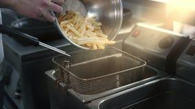El cocinero llena la sartén de la patata cruda para hacer las fritadas en la cámara lenta, haciendo las patatas fritas en aceit almacen de video