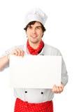 El cocinero lleva a cabo un espacio en blanco blanco Imagenes de archivo