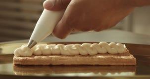 El cocinero negro puso el crem en la pasta de hojaldre del bolso de los pasteles metrajes