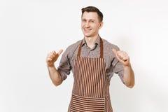 El cocinero o el camarero confiado sonriente joven del hombre en el delantal marrón rayado, camisa señalando los fingeres en sí m imagen de archivo