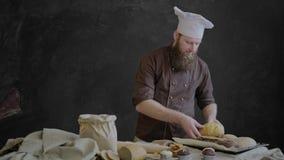 El cocinero pone coció recientemente el pan en una bandeja que cuece, adornando la tabla con los pasteles de su panadería almacen de video