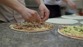El cocinero pone el jam?n encima de los otros ingredientes en el c?rculo de la pasta de la pizza y cocinar de los finales metrajes