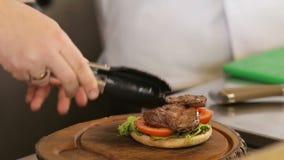 El cocinero pone la carne en un pan de la hamburguesa almacen de video