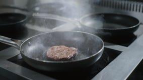 El cocinero pone la chuleta cruda de la carne de vaca a la cacerola caliente en la cocina en la cámara lenta, carne del restaura almacen de video