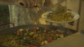 El cocinero pone la paella caliente con los mejillones, los camarones, el calamari y los pimientos picantes de la cacerola Hombre almacen de metraje de vídeo