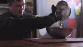 El cocinero pone la pasta del pequeño cuenco el más grande usando cierre de la cuchara La figura del cocinero se empaña Preparaci almacen de video