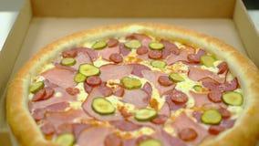 El cocinero pone la pizza cocinada con tocino y la salchicha ahumada en una caja para la entrega adicional almacen de metraje de vídeo