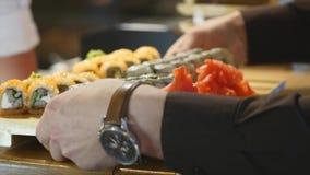 El cocinero pone las placas con el sushi y rueda en la tabla y el camarero las toma El rollo Philadelphia es uno de la más popula metrajes