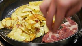 El cocinero pone los pedazos de carne en la cacerola, donde las patatas se fríen en aceite almacen de metraje de vídeo