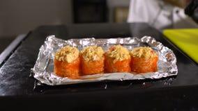 El cocinero pone los rollos de sushi en la hoja Cocinar platos japoneses metrajes