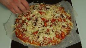 El cocinero pone el queso en un primer crudo de la pizza metrajes