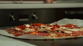 El cocinero pone el queso en un primer crudo de la pizza almacen de metraje de vídeo