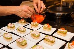 El cocinero preparó arrancadores gastrónomos deliciosos del canapé en las placas blancas Imágenes de archivo libres de regalías