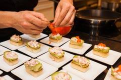 El cocinero preparó arrancadores gastrónomos deliciosos del canapé en las placas blancas Imagenes de archivo