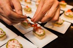 El cocinero preparó arrancadores gastrónomos deliciosos del canapé en las placas blancas Fotografía de archivo