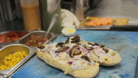 El cocinero prepara el bocadillo del queso de la tostada con la cebolla y las setas metrajes