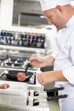 El cocinero prepara el filete de carne de vaca en cacerola en la cocina Imágenes de archivo libres de regalías
