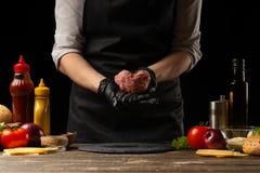 El cocinero prepara la chuleta con la carne picada fresca, sosteni?ndose bajo la forma de coraz?n, los ingredientes en el fondo,  fotografía de archivo libre de regalías