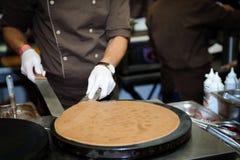 El cocinero prepara la crepe imagenes de archivo