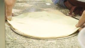 El cocinero prepara la pasta para la pizza