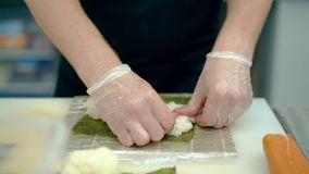 El cocinero prepara los rollos japoneses, arroz de las pilas en alga marina del nori almacen de video