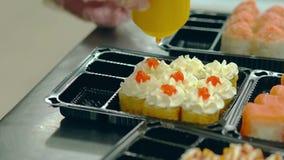 El cocinero prepara los rollos japoneses con una tortilla frita, añade salmones rojos del caviar almacen de metraje de vídeo