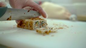 El cocinero prepara un rollo japonés, adornado con la piel asada de los pescados de la anguila, las masas flotantes metrajes