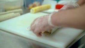El cocinero prepara un rollo japonés con los salmones metrajes