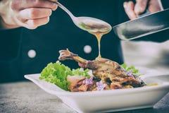 El cocinero prepara una comida gastrónoma Foto de archivo