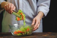 El cocinero prepara una ensalada vegetal vegetariana fotos de archivo