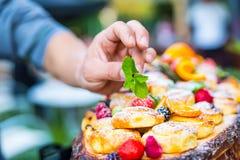 El cocinero prepara una placa de tortas con las frutas frescas Él está trabajando en la decoración de la hierba Fiesta de jardín  Imagen de archivo