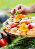 El cocinero prepara una placa de tortas con las frutas frescas Él está trabajando en la decoración de la hierba Fiesta de jardín  Imagen de archivo libre de regalías