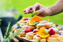 El cocinero prepara una placa de tortas con las frutas frescas Él está trabajando en la decoración de la hierba Fiesta de jardín  Foto de archivo